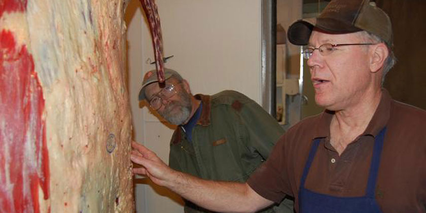 Mike Berger of Peabody Sausage House tells JFF Farm Manager Norm Oeding about a side of JFF beef dry-aging at the meat locker, Dec 2011.